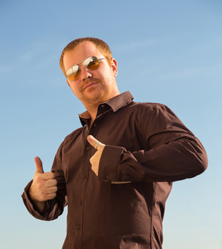 Modern man showing OK sign with his thumb up. Young man in sunglasses against the blue sky. Selective focus on face. Young handsome man with thumbs up. Male model showing success.